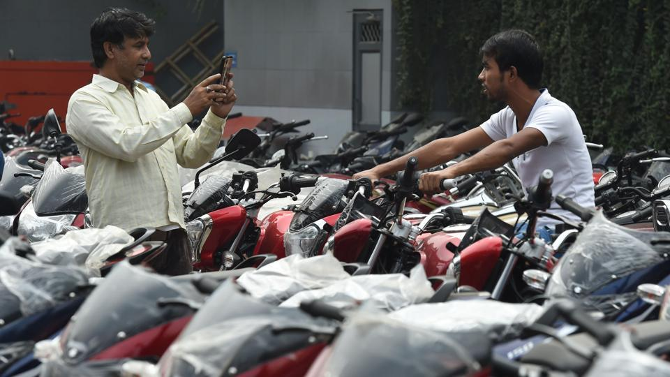 A man poses for a picture sitting on a BS-IV standard motorcycle at a showroom in New Delhi.