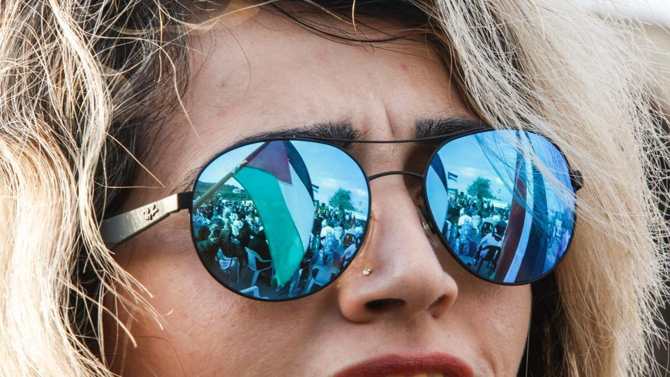 A picture taken on March 30, 2017 shows a reflection through the lenses of a female demonstrator's sunglasses of a Palestinian flag flying during a demonstration of Arab-Israelis marking Land Day in the northern Arab-Israeli village of Deir Hanna in the northern Galilee region. (HAZEM BADER / AFP)