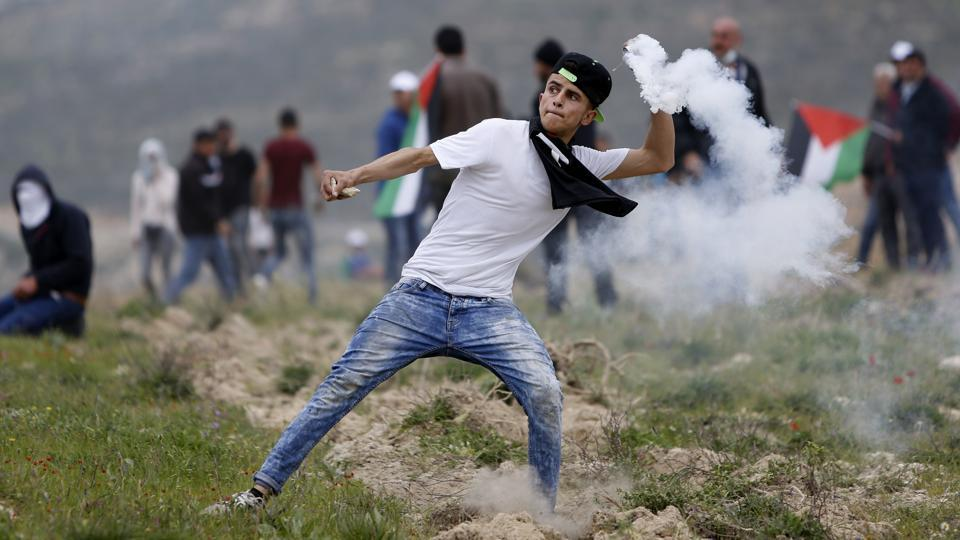 Palestinian youth throws back teargas canister during clashes with Israeli forces following a protest to mark the Land Day near the village of Madama, south of the West Bank city of Nablus. (Majdi Mohammed / AP)