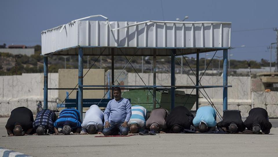 Palestinian residents of Gaza Strip pray as they wait on the Israeli side of the Erez terminal to cross to Gaza Strip.