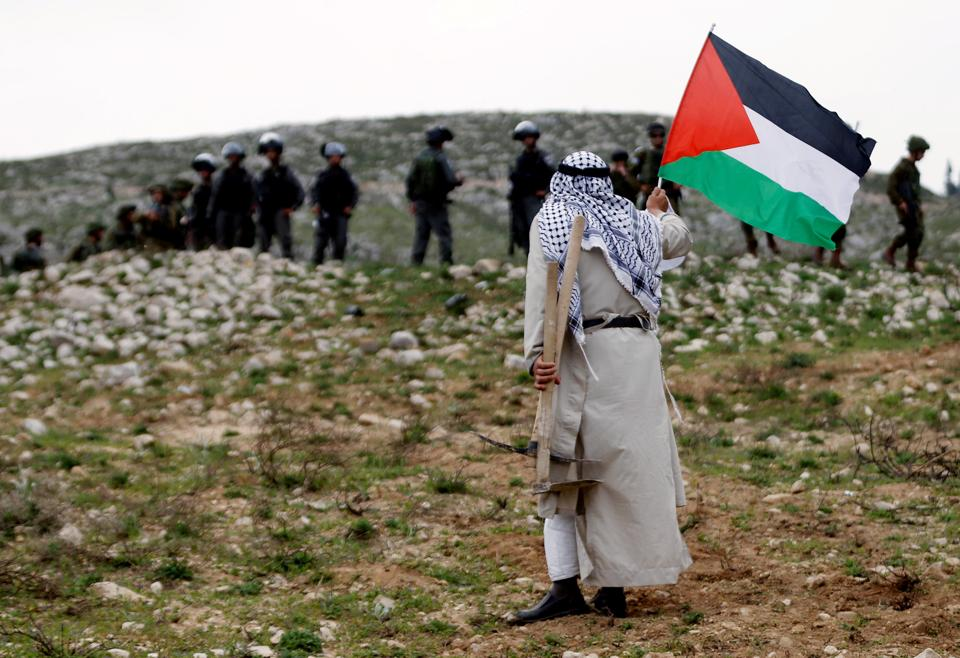 A man holds a Palestinian flag in front of Israeli troops during a protest marking Land Day in the West Bank village of Madama, near Nablus. (Mohamad Torokman / REUTERS)