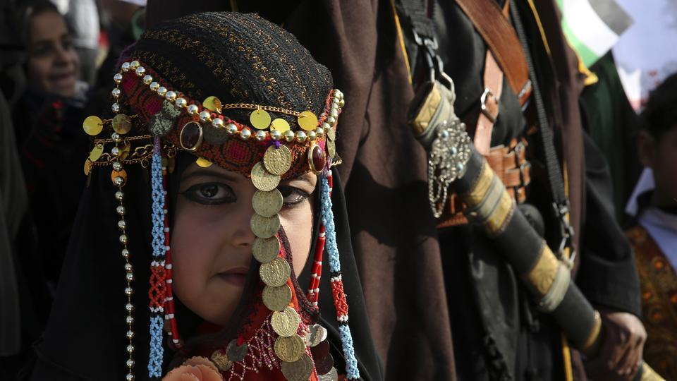 A bedouin girl wears traditional dress attend a rally marking the 41st anniversary of Land Day, in Deir el-Balah, Central Gaza Strip, Friday, March 31, 2017.Land Day commemorates riots on March 30, 1976, when many were killed during a protest by Israeli Arabs whose property was annexed in northern Israel to expand Jewish communities. (Adel Hana / AP)