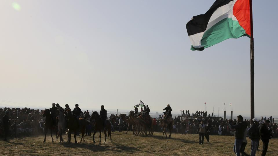 Bedouin youths ride their camels and horses during a rally marking the 41st anniversary of Land Day, in Deir el-Balah, Central Gaza Strip. (Adel Hana / AP)