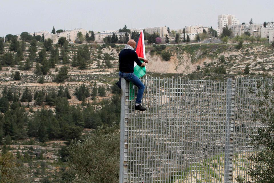 A Palestinian man plants his national flag atop an iron fence, setup by Israeli security forces, between the Palestinian village of Beit Jala and the Jerusalem area, on March 30, 2017 during Land Day protest. (Musa AL SHAERAFP)