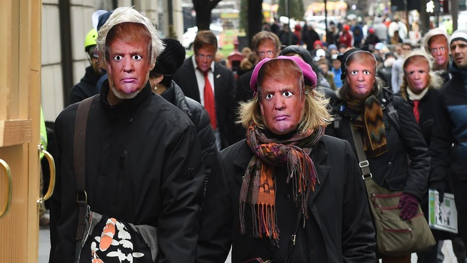 """People wearing masks of US President Donald Trump take part in the 32nd Annual April Fools' Day Parade in New York. The theme for this year's parade is """"MAKE RUSSIA GREAT AGAIN!"""""""