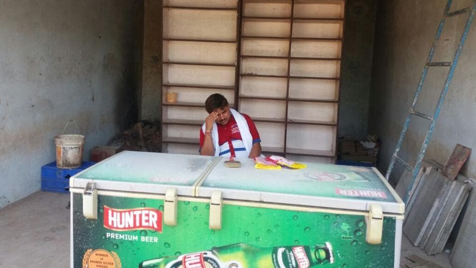A sales attendant dejectedly takes stock of the situation after villagers ransacked his liquor shop at Khimlasa in Sagar district.