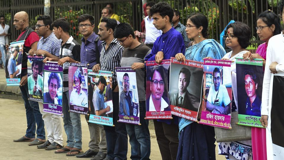 Activists in Dhaka hold photos of writers and bloggers who were murdered in the last few years.