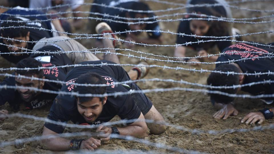 The 5km running course was designed with over 20 military-style obstacles that saw participants clinch their teeth as they ran through muddy tracks, slush pits, tunnels, climb crafted walls to reach the finish line. (Arijit Sen/HT Photo)
