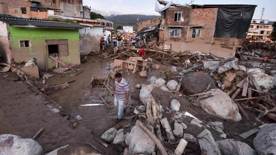 People walk through the rubble left by mudslides following heavy rains in Mocoa. Several deadly landslides have struck Colombia in recent months. (Luis Robayo/AFP)
