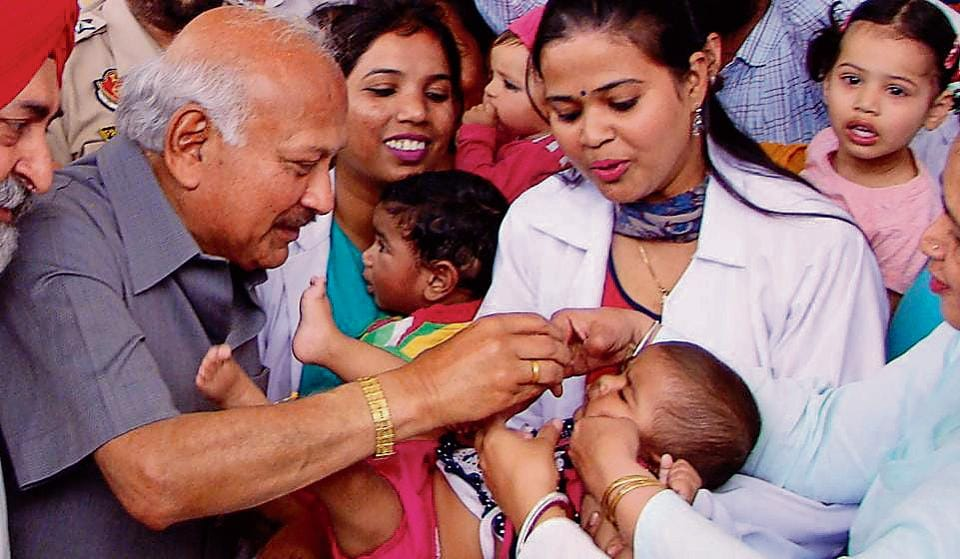 Punjab health minister Brahm Mohindra administering polio drops to a child during a Pulse Polio campaign at Tripuri town in Patiala on Sunday.