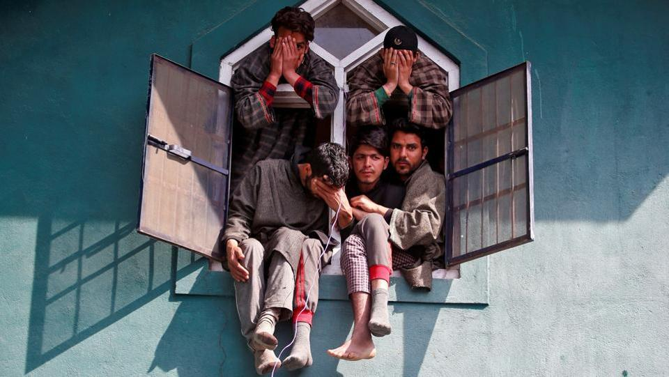People react as they sit in a window of a mosque during the funeral of Tauseef Ahmad Wagay, a suspected militant, who according to local media was killed in a gun battle with Indian army on Tuesday in Chadoora, in Yaripora, in south Kashmir's Kulgam district on March 29, 2017.  (Danish Ismail/REUTERS)