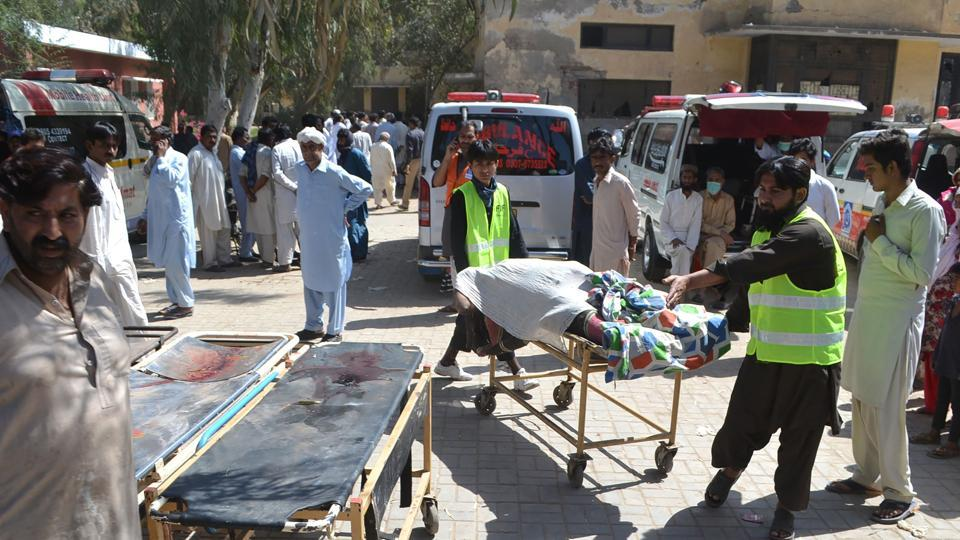 Volunteers transport the body of a victim murdered at a Sufi shrine on the outskirts of Sargodha District in Punjab province on Sunday.