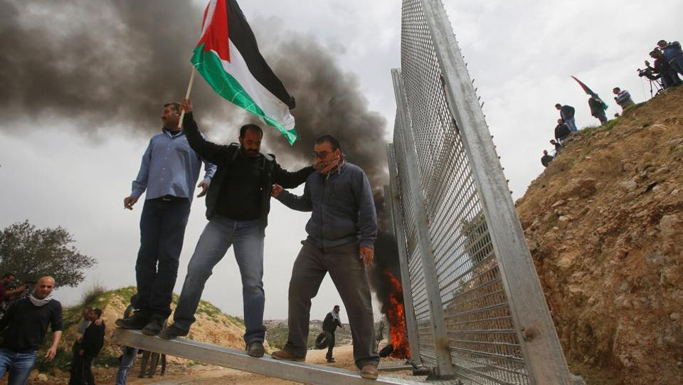 Palestinian demonstrators try to remove a section of the Israeli barrier fence during a protest marking Land Day in the West Bank city of Beit Jala on March 30, 2017. (Mussa Qawasma/REUTERS)