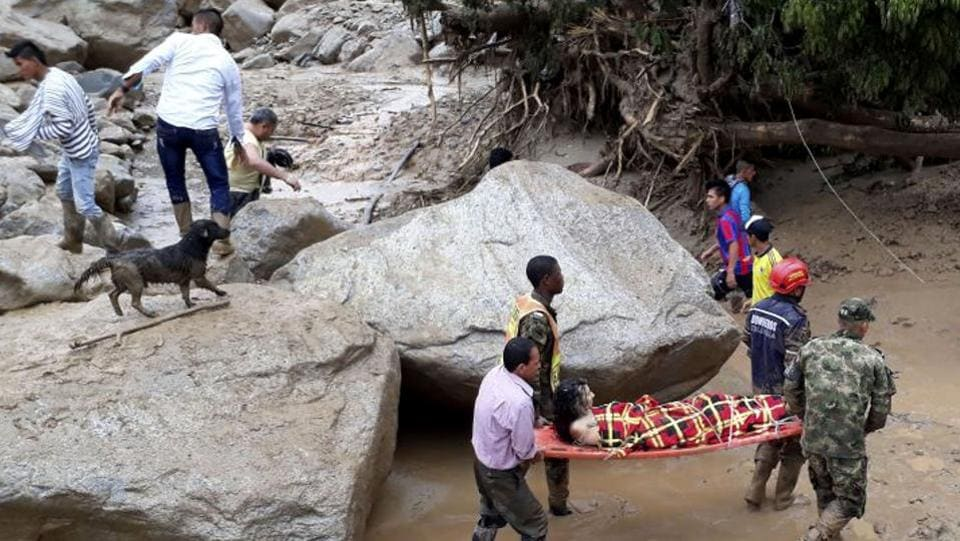 Rescuers carry a woman after heavy rains caused a nearby river to overflow and surge mud and debris into Mocoa. Climate change can play a big role in the scale of natural disasters, such as this one, a senior UN official said. (NYT)