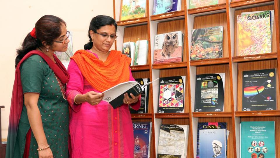 Experts read an academic journal at a library.