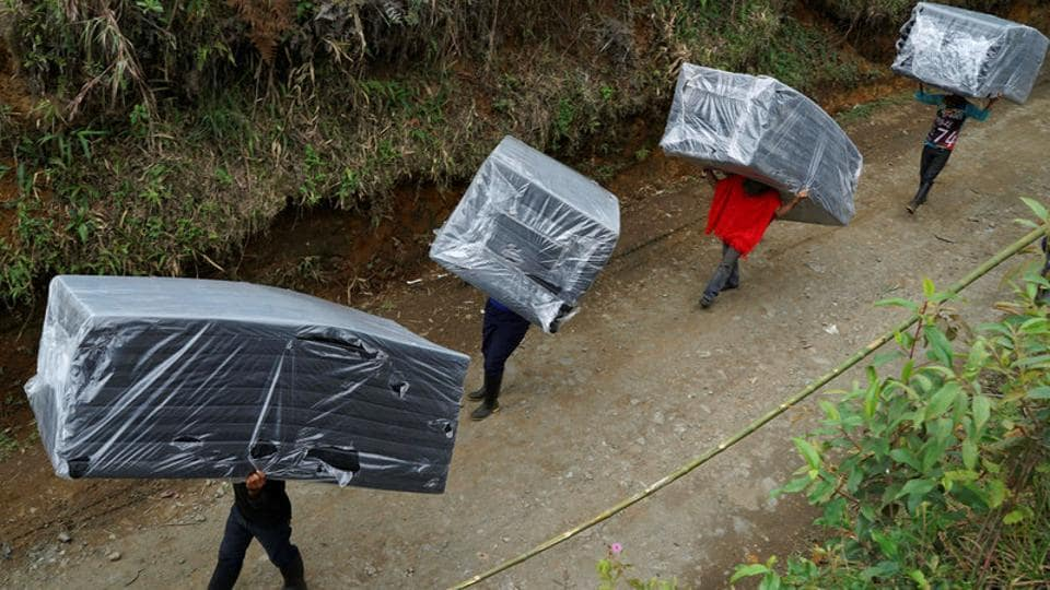 FARC members carry mattresses to their tents in a camp near the transitional zone of Pueblo Nuevo. Members of the Jacobo Arenas rebel unit, which operated in mountains of Cauca province, were among 6,900 FARC fighters who left behind clandestine camps where they had lived for decades, crisscrossing the country on foot, by boat and by truck to get to 26 zones monitored by the United Nations. (Federico Rios/REUTERS)