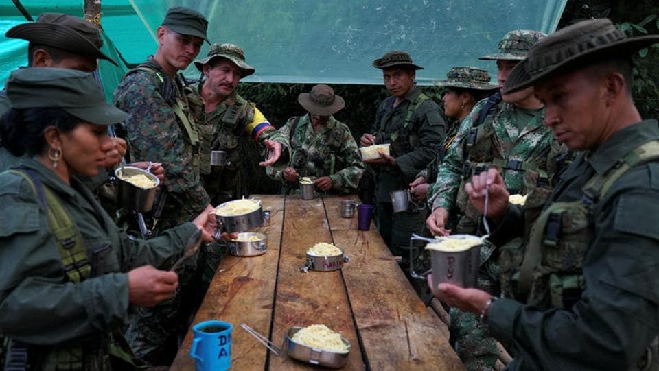 FARC members eat their last dinner before moving troops to Pueblo Nuevo. The government says it is working as quickly as possible to finish each camp, that the FARC is partly responsible for construction and that the facilities are far superior to the tarp and bamboo lean-tos traditionally used by the rebels. (Federico Rios/REUTERS)