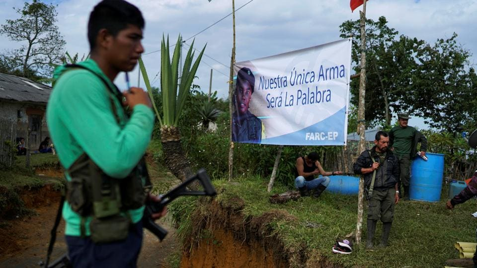 FARC members guard an entrance of a camp near the transitional zone of Pueblo Nuevo in the Cauca mountains. A first version was narrowly rejected in a referendum last year, before being modified and passed by Congress. (Federico Rios/REUTERS)