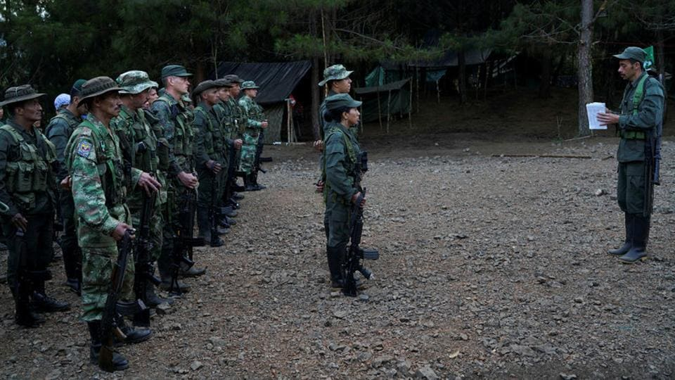 FARC members stand during a formation at the Los Robles FARC camp, Colombia. Weapons handed over to the United Nations will be stored in secure containers until they can be turned into three memorial statues. (Federico Rios/REUTERS)