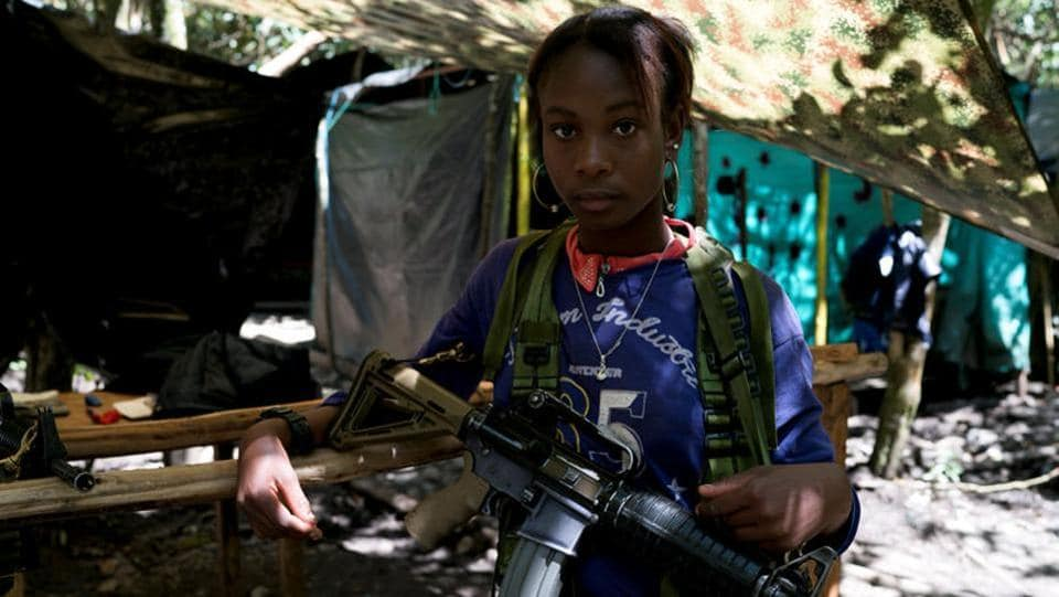 Angela, a FARC member, stands in a camp near La Elvira transitional zone in Los Robles. Some FARC members have told local media they will not hand over their weapons until the camps are more habitable for fighters, who are well used to rough-and-tumble living conditions in poverty-stricken rural areas. (Federico Rios/REUTERS)