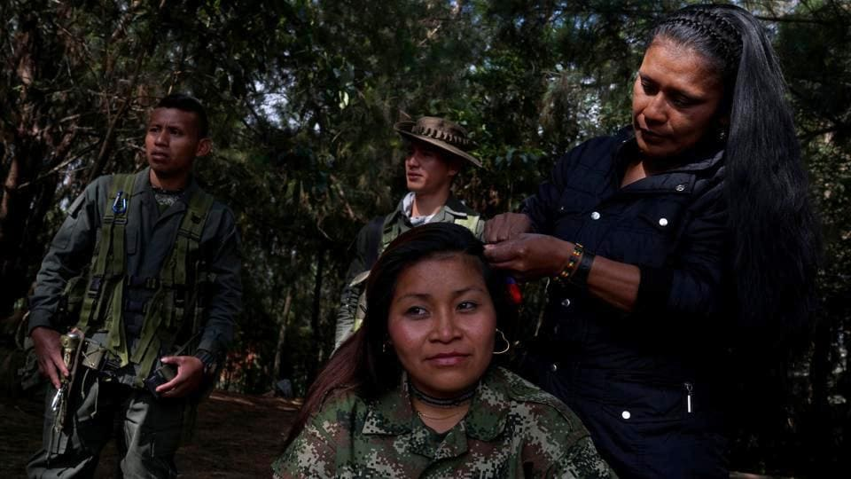 Karina gets her hair done by a friend in a camp while waiting for a truck to move to the transition zone of Pueblo Nuevo, at the Los Robles FARC camp, Colombia. Former fighters from Colombia's FARC rebel group are handing over thousands of weapons and other materials to international officials in special camps, as the group's six-month disarmament process continues. (Federico Rios/REUTERS)