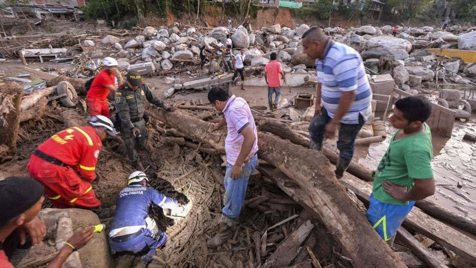 Rescuers seek people among the rubble left by mudslides following heavy rains in Mocoa. Rescuers clawed through piles of mud and twisted debris Sunday searching for survivors after violent mudslides destroyed homes in southern Colombia, killing over 200 people and injuring hundreds more. (Luis Robayo/AFP)