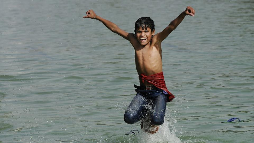 A boy jumps into a water channel near India Gate to get respite from the heat in New Delhi, India on March 29, 2017. (Burhaan Kinu/HT PHOTO)