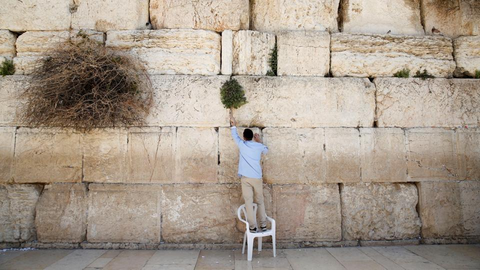 A man clears notes placed in the cracks of the Western Wall, Judaism's holiest prayer site, to make space for new notes ahead of the Jewish holiday of Passover, in Jerusalem's Old City on March 29, 2017.  (Baz Ratner /REUTERS)