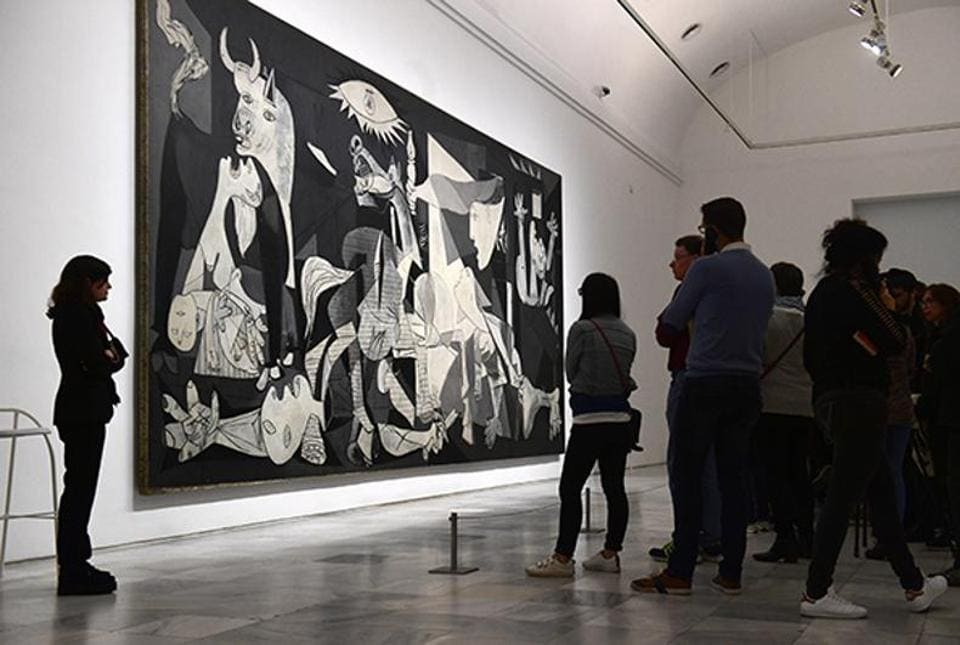 Visitors look at Spanish artist Pablo Picasso's painting, Guernica at Reina Sofia museum in Madrid on March 24, 2017.