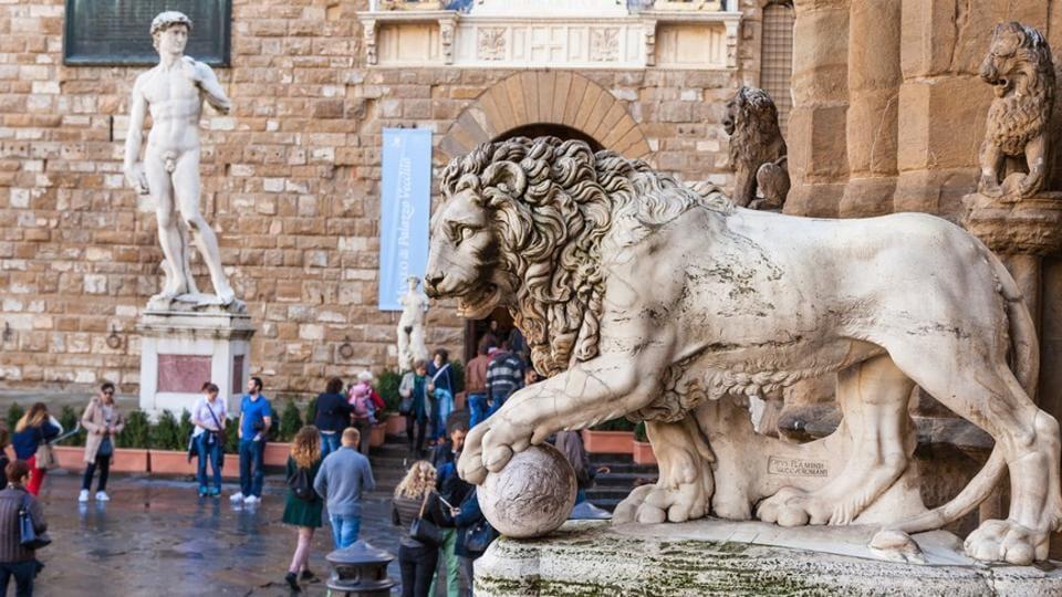 Medici Lion in Loggia dei Lanzi and entrance of Palazzo Vecchio town hall on Piazza della Signoria in Florence, Italy.