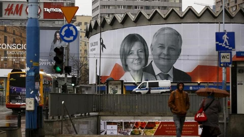 People walk in front of a giant picture of late Polish president Lech Kaczynski and his wife Maria, who died six years ago when a Polish government plane crashed in Smolensk, Russia, hanging on a building in the centre of Warsaw, Poland April 10, 2016.