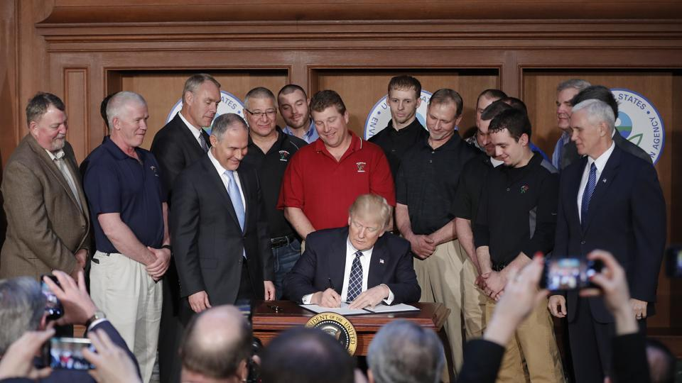 In this March 28, 2017, photo, President Donald Trump, accompanied by Environmental Protection Agency (EPA) Administrator Scott Pruitt, third from left, and Vice President Mike Pence, right, signs an Energy Independence Executive Order at EPA headquarters in Washington.