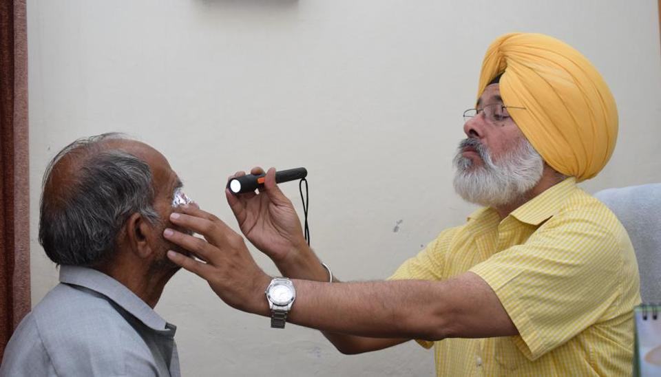 District programme manager Dr Shamsher Singh examining a patient at civil hospital in Jalandhar on Saturday.