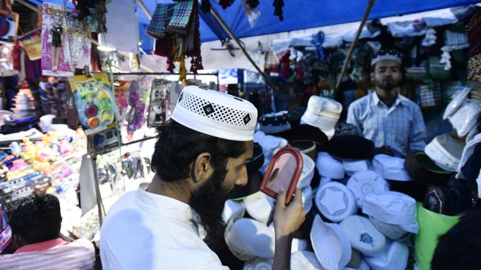 A devotee checks his scull cap before buying it from the market at shrine of Sufi saint Hazrat Khwaja Syed Nizamuddin Auliya. (Burhaan Kinu/HT PHOTO)