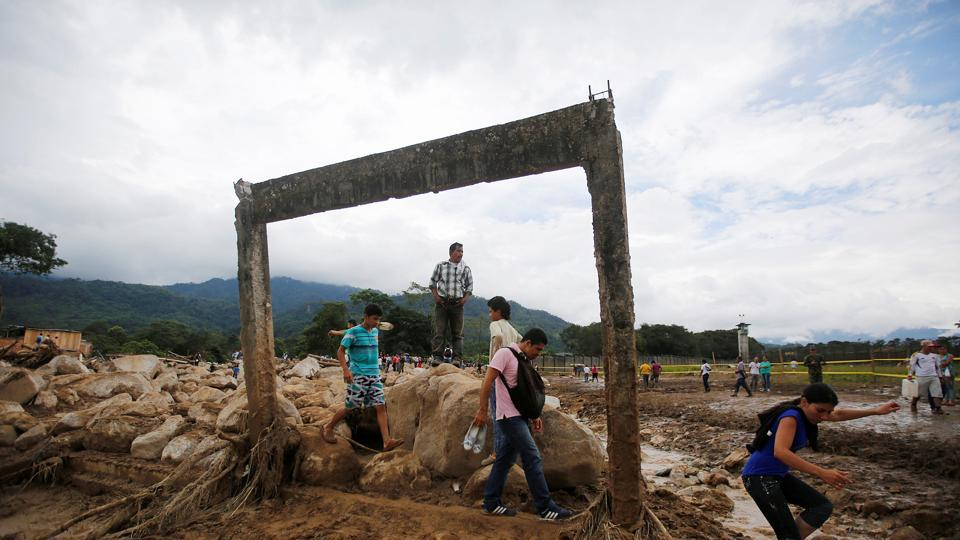 People walk in a destroyed area after flooding and mudslides caused by heavy rains in Mocoa, Colombia, on April 2.