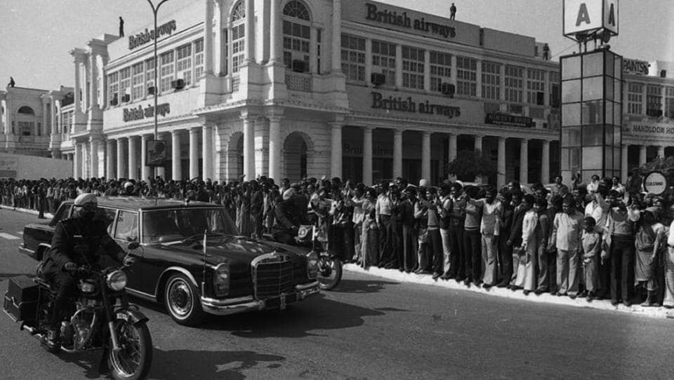 People queue up to see Queen Elizabeth II's cavalcade crossing Connaught Place on 17 November 1983 in New Delhi. A recent report has listed Connaught Place at 9th position in the list of most expensive prime office and commercial business districts in the world. A look back at the HT archives on how it has changed over the decades. (SN Sinha/HT Photo )