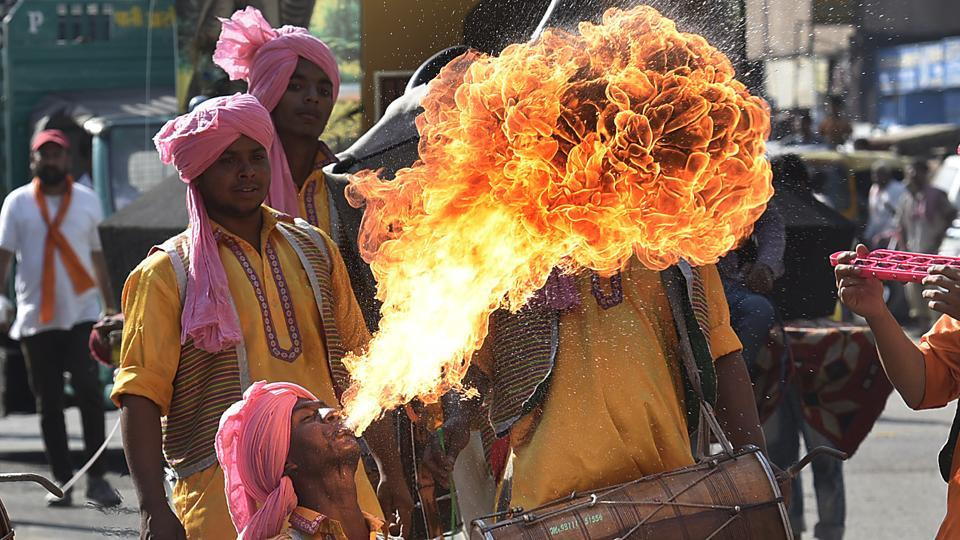 A fire-eater from Punjab performs to the heady beat of the traditional dhol. Participants from various states danced, sang and performed as they walked the 5km long rally. (Raj K Raj/HT PHOTO)