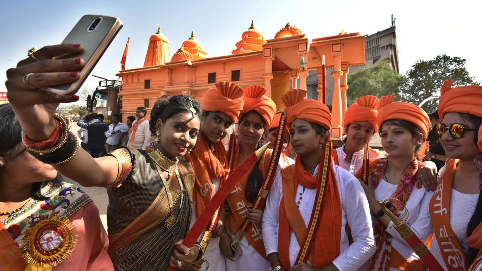 A woman dressed as Jhansi ki Rani, left, takes a selfie with members VHP women's wing Durga Vahini in front of Ram Mandir replica.  (Raj K Raj/HT PHOTO)
