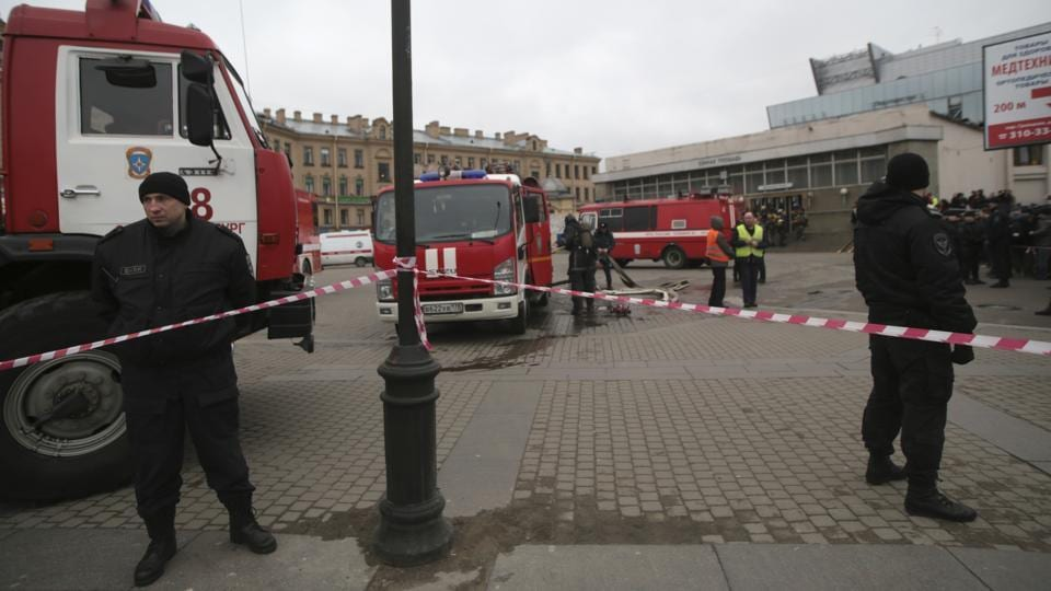 Russian police and emergency service officers stand near fire trucks near the entrance of Sennaya Square subway station in St Petersburg. Russia's health minister said out of 10 people, 7 died at the scene, 1 en route to hospital and 2 in hospital. (Evgenii Kurskov/AP)
