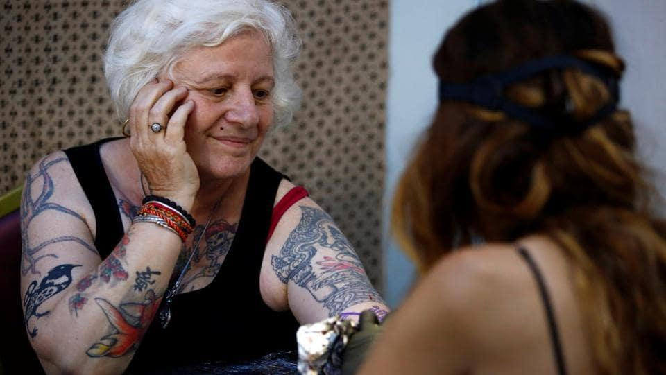 A woman smiles as she gets a tattoo . (Navesh Chitrakar / Reuters)