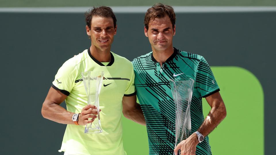 Rafael Nadal of Spain (L) and Roger Federer of Switzerland (R) hold the finalist and Butch Buchholz trophy, respectively, after their match in the men's singles championship of the 2017 Miami Open at Crandon Park Tennis Center. Federer won 6-3, 6-4.