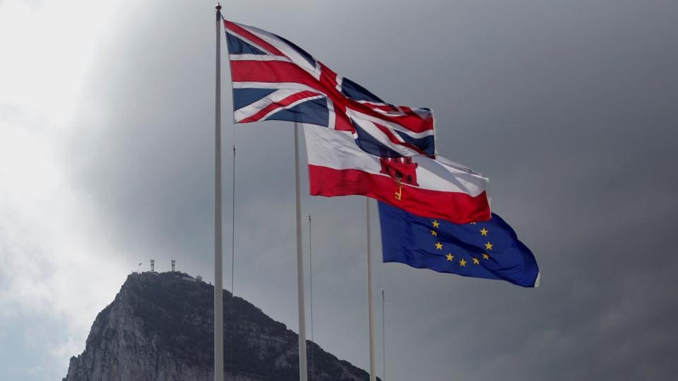 The Union Jack (left), the Gibraltarian flag (centre) and the European Union flag are seen flying, at the border of Gibraltar with Spain, in front of the Rock in the British overseas territory of Gibraltar, historically claimed by Spain.