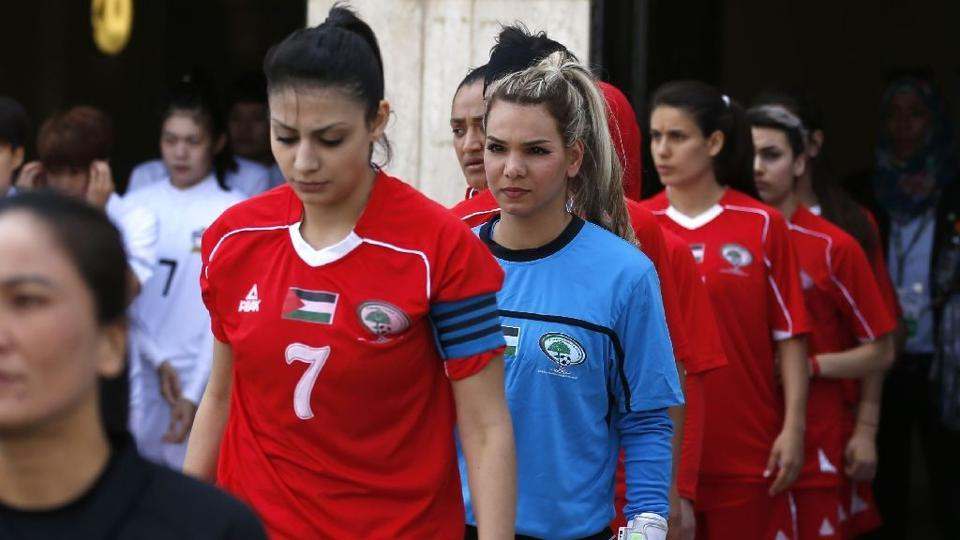 Players from the Palestinian women's football team take to the pitch for a qualifying match against Thailand on April 3, 2017.