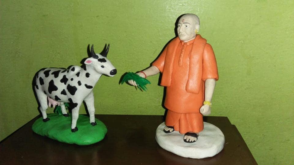 Wax-clay model of chief minister Yogi Adityanath feeding a cow.