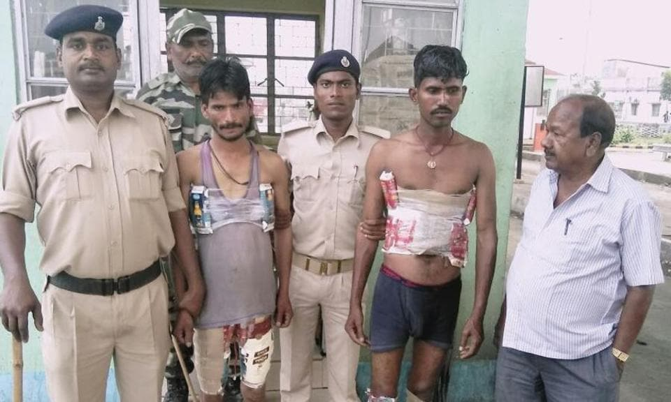 Cops with arrested youth who had strapped liquor to their bodies in Purnea.