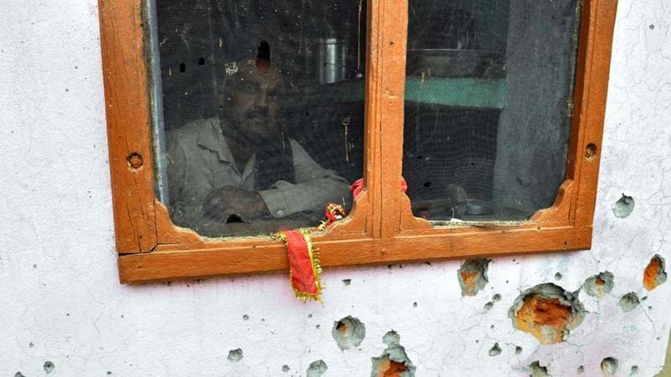 A villager looks through the window of his house damaged in firing by Pakistan at Chilyari village, Samba in Jammu.  Pakistan Army fired at Indian posts along the LoC in Rajouri district on April 4, 2017.