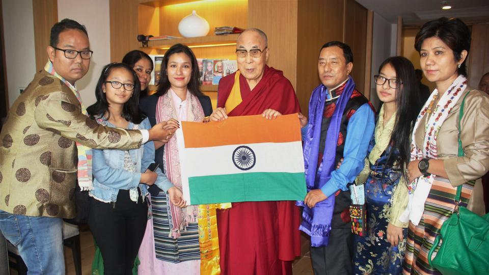 The Dalai Lama presents the Indian National Flag to mountaineer Anshu Jamsenpa during the flagging off ceremony of her Mt Everest expedition in Guwahati on Monday.