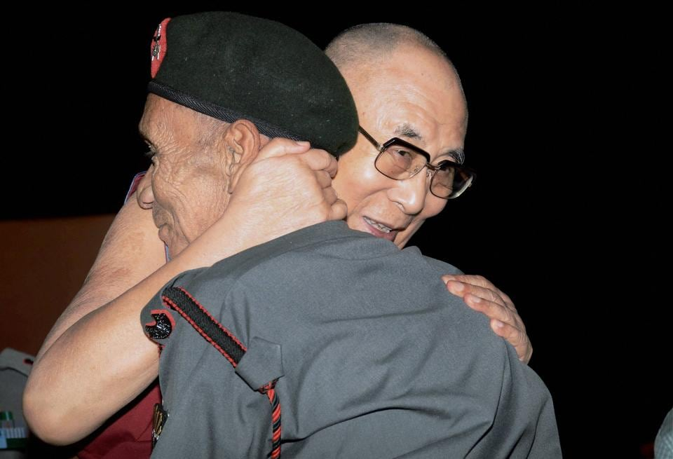Tbetan spiritual leader the Dalai Lama hugs retired Assam Rifles guard Naren Chandra Das, the lone known survivor of a group of seven Indian personnel who were the first to receive the Dalai Lama on Indian soil after he fled Tibet, during an event in Guwahati . (PTI.)