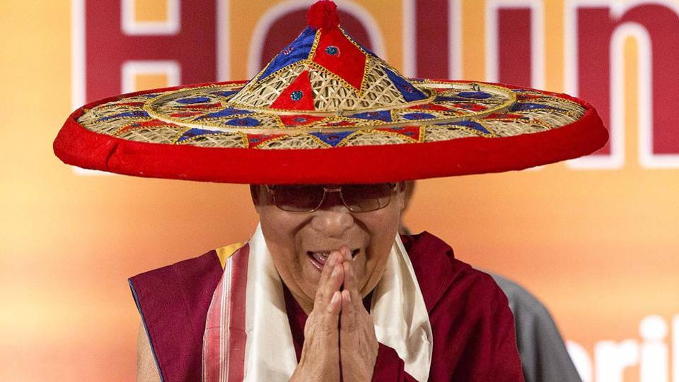 Tibetan spiritual leader Dalai Lama wears a Japi, a traditional Assamese head gear, and greets the audience during the platinum jubilee celebrations of Assam Tribune newspaper . (Anupam Nath / AP)