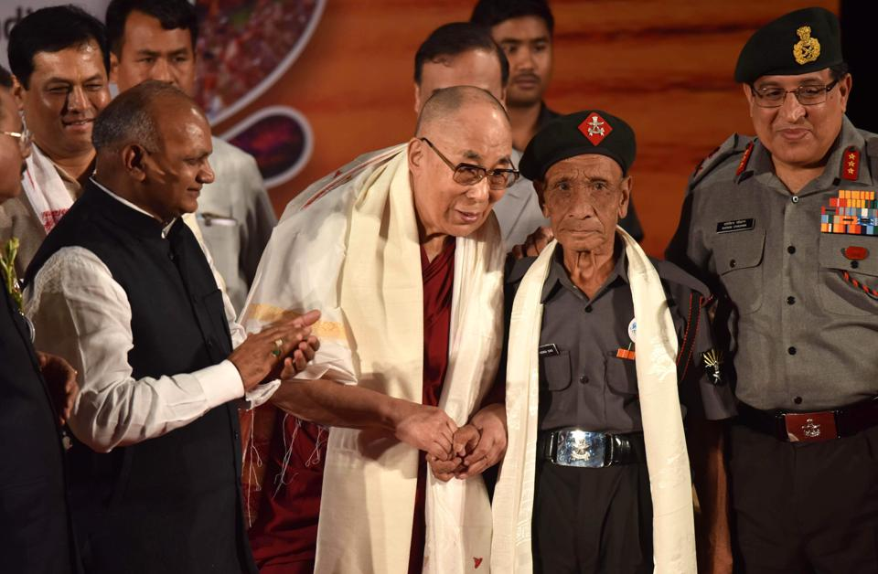 Tibetan spiritual leader the Dalai Lama (L) shakes hands with retired Assam Rifles personnel Naren Chandra Das. The Dalai Lama has had an emotional reunion with the Indian border guard who escorted him as he fled his native Tibet following a failed uprising nearly 60 years ago. The 81-year-old Tibetan spiritual leader, who has lived in exile ever since, was visibly emotional as he embraced the retired paramilitary guard on April 2 at the start of a visit to northeast India that has angered China.  (Biju BORO / AFP)